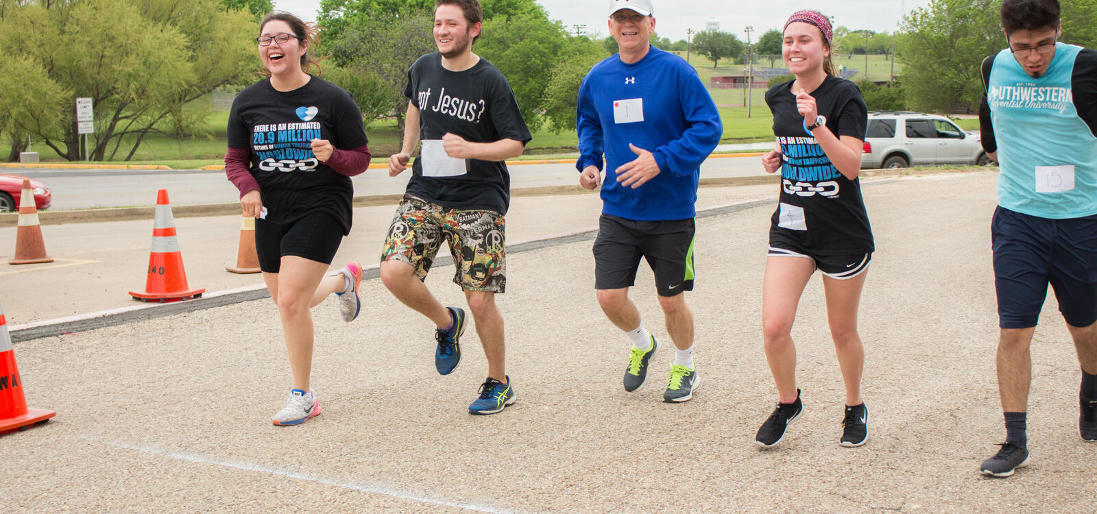 Four students smile and laugh as they run along side the University's President, Dr. Shaw.