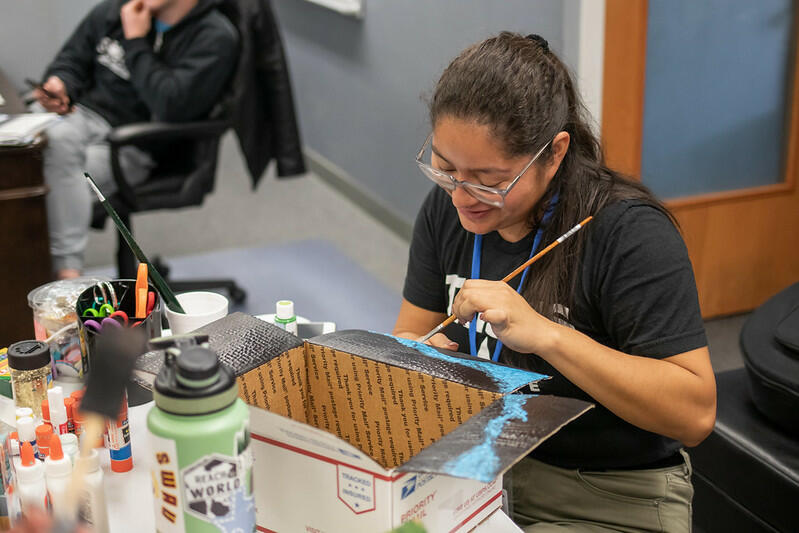 Sitting in front of a table full of art supplies, a female student, with her hair tied up in a ponytail, smiles as she paints the flaps of a box