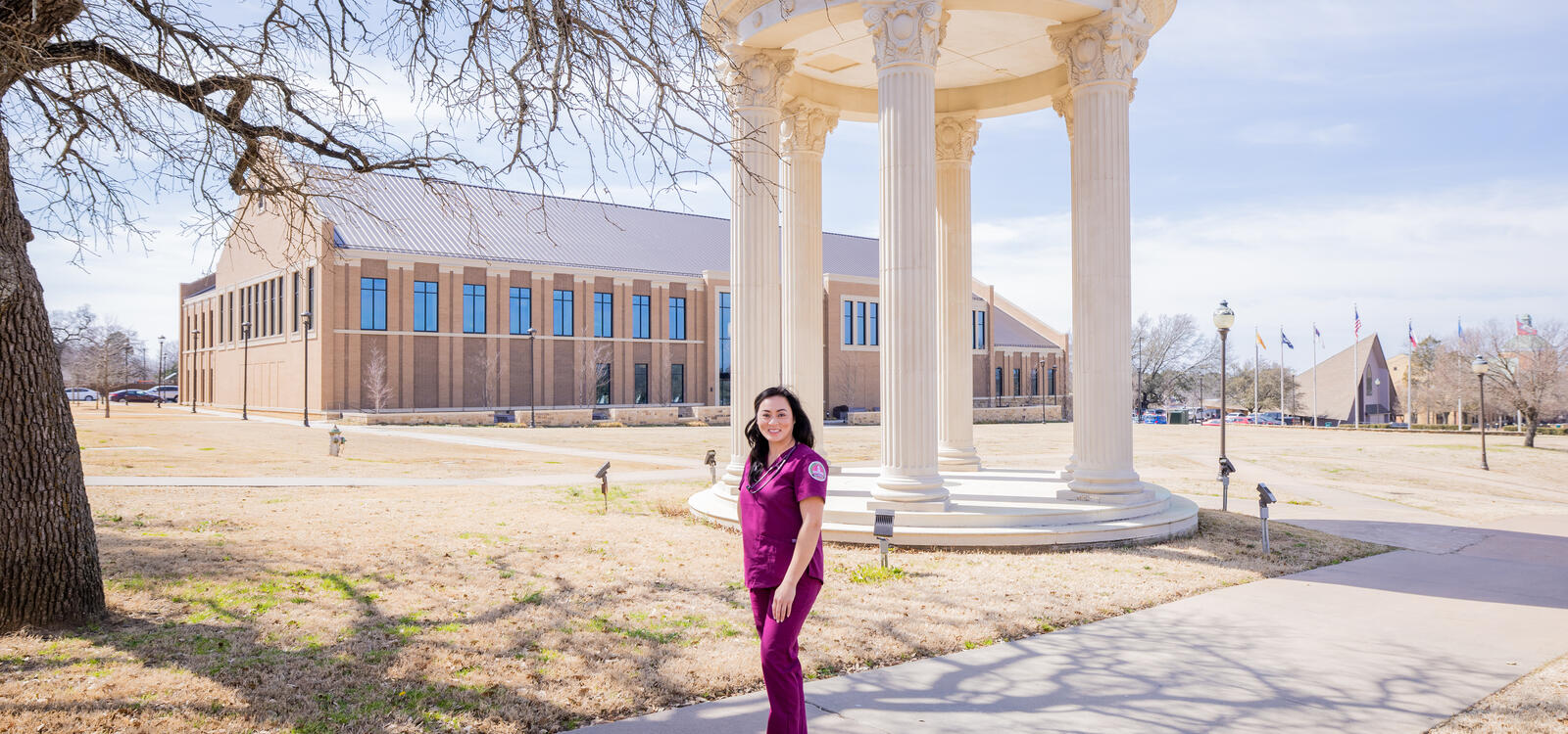 Linh Vu poses in SWAU scrubs in front of the rotunda with the nursing building in the background