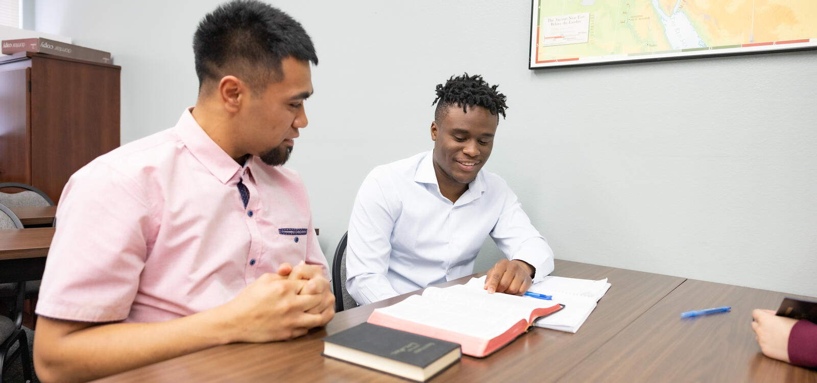 Two male students studying the Bible together and smiling.