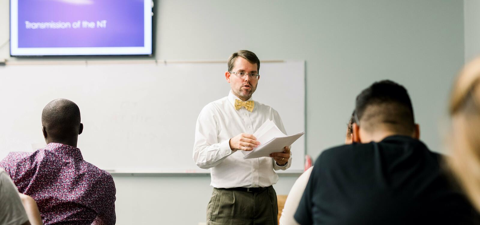 Dr. Campbell, dressed in a white buttoned shirt and yellow bow-tie, stands in front of his class and holds papers as he begins to hand them out to his students