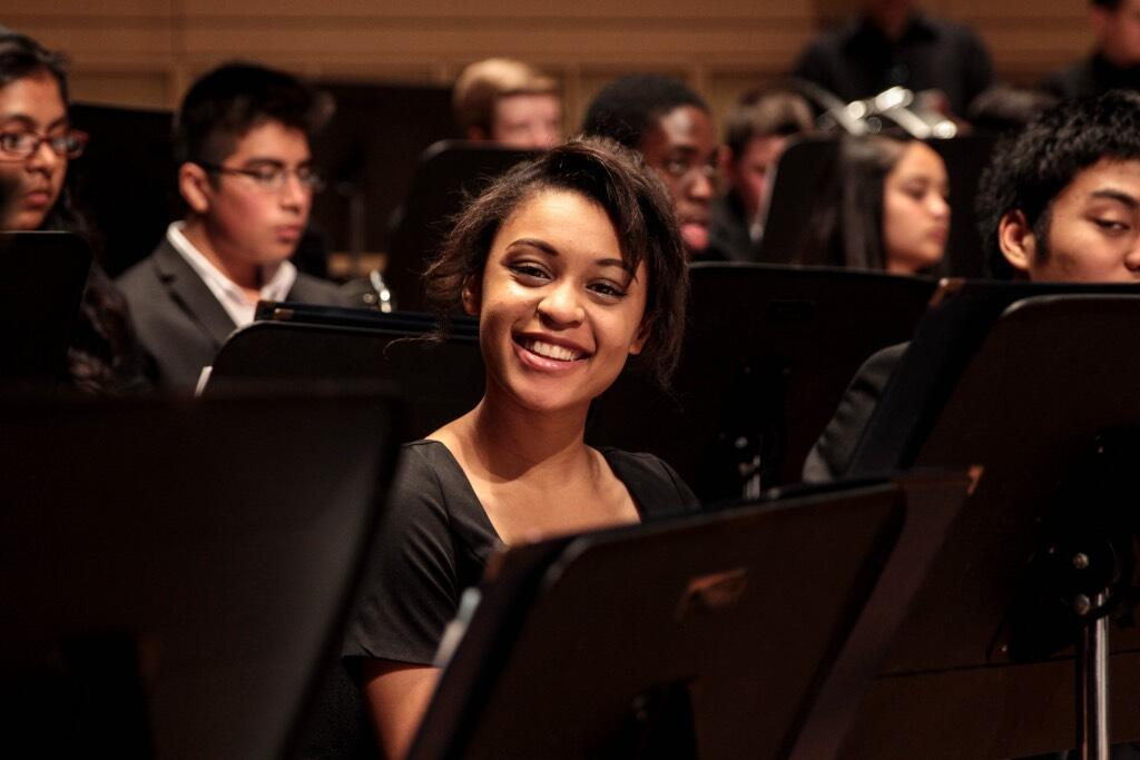 A young student smiles as she sits among her peers waiting to practice their piece