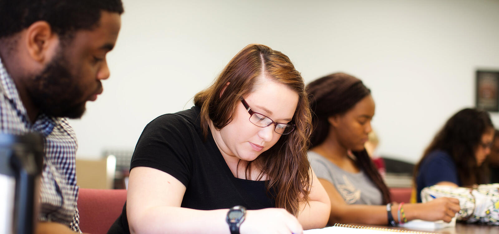 Sitting at a rectangular table beside her peers, a student looks down and reviews her notes