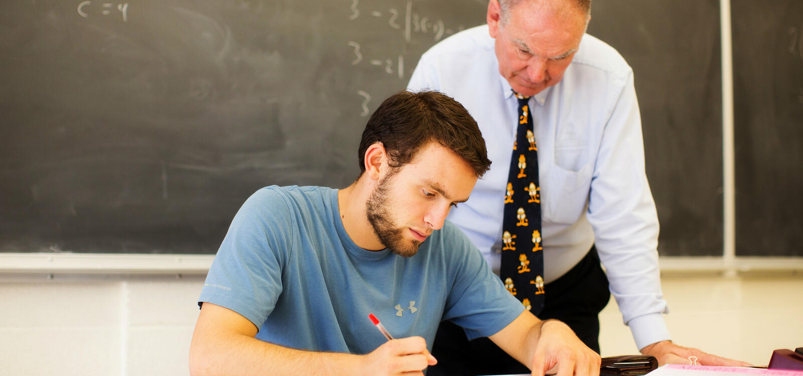 A student sits at a desk and completes his homework as his professor stands behind him to help