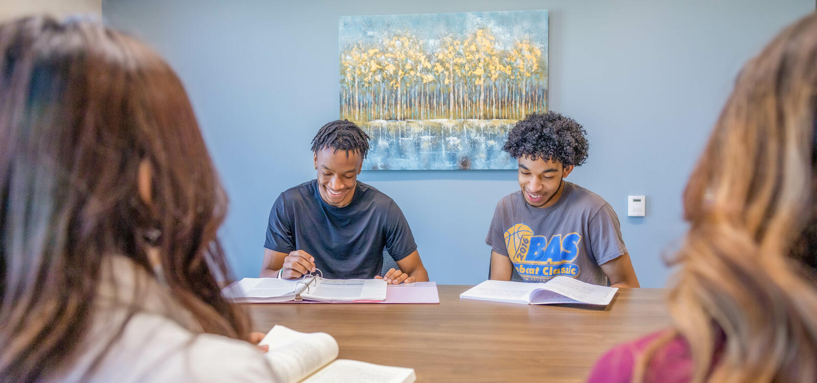 Two male students smiling and reviewing with other students.