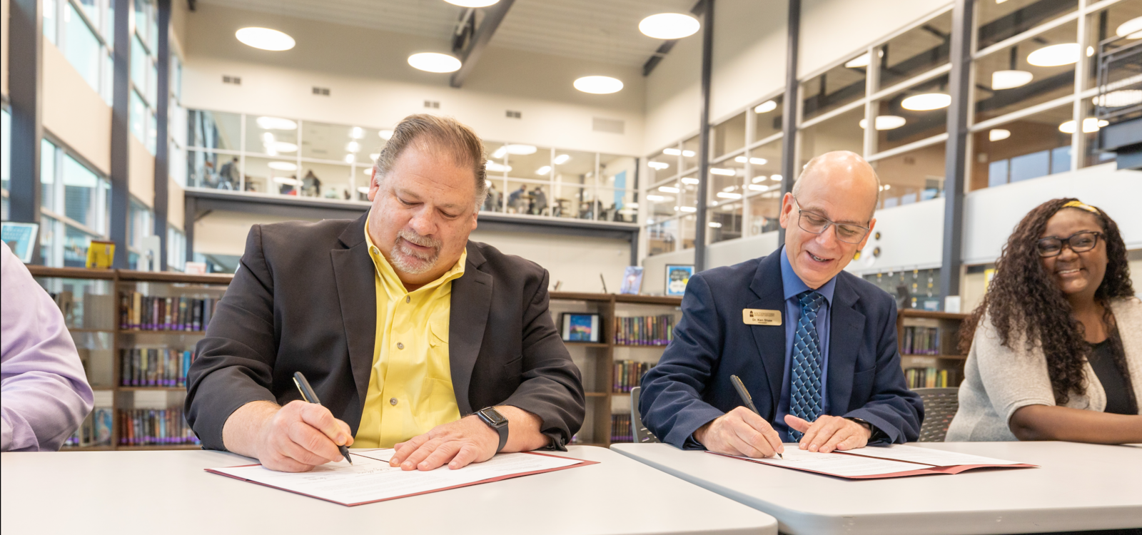 Dr. Shaw and another man sign papers on tables in a library