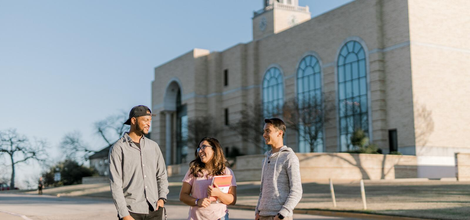 Standing outside in front of the library, three students stop to talk