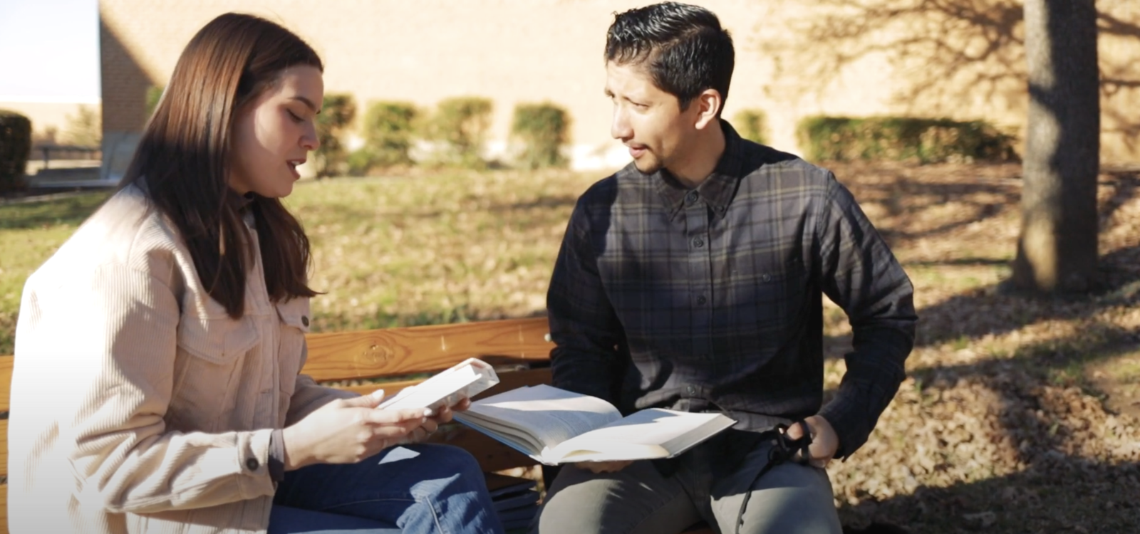 Two students sit on a bench holding books and talking
