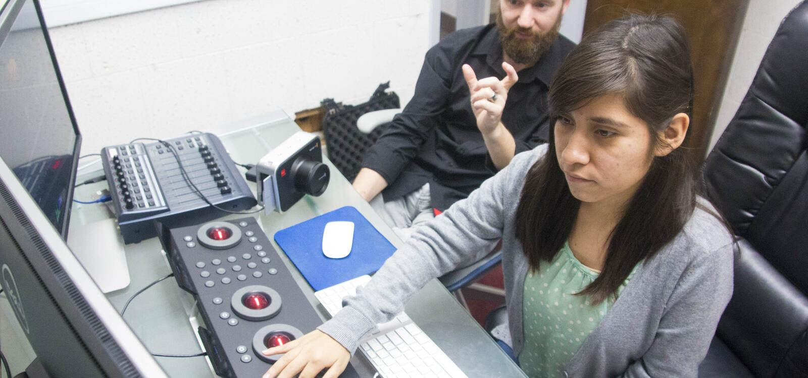 Sitting in front of a keyboard of buttons and balls, a student makes adjustments as she looks at two screens.
