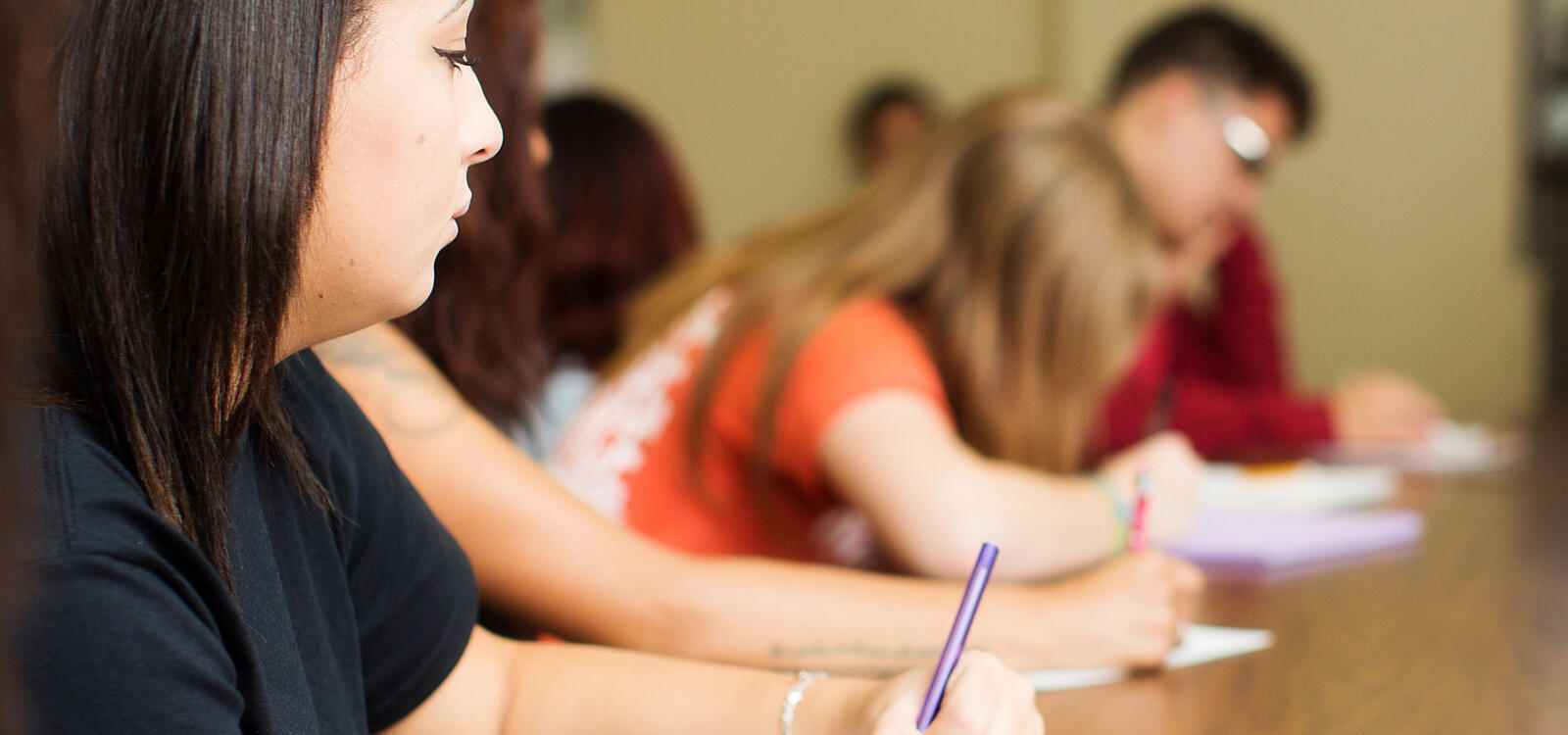 A female student sits with her peers as they all begin writing on their notepads