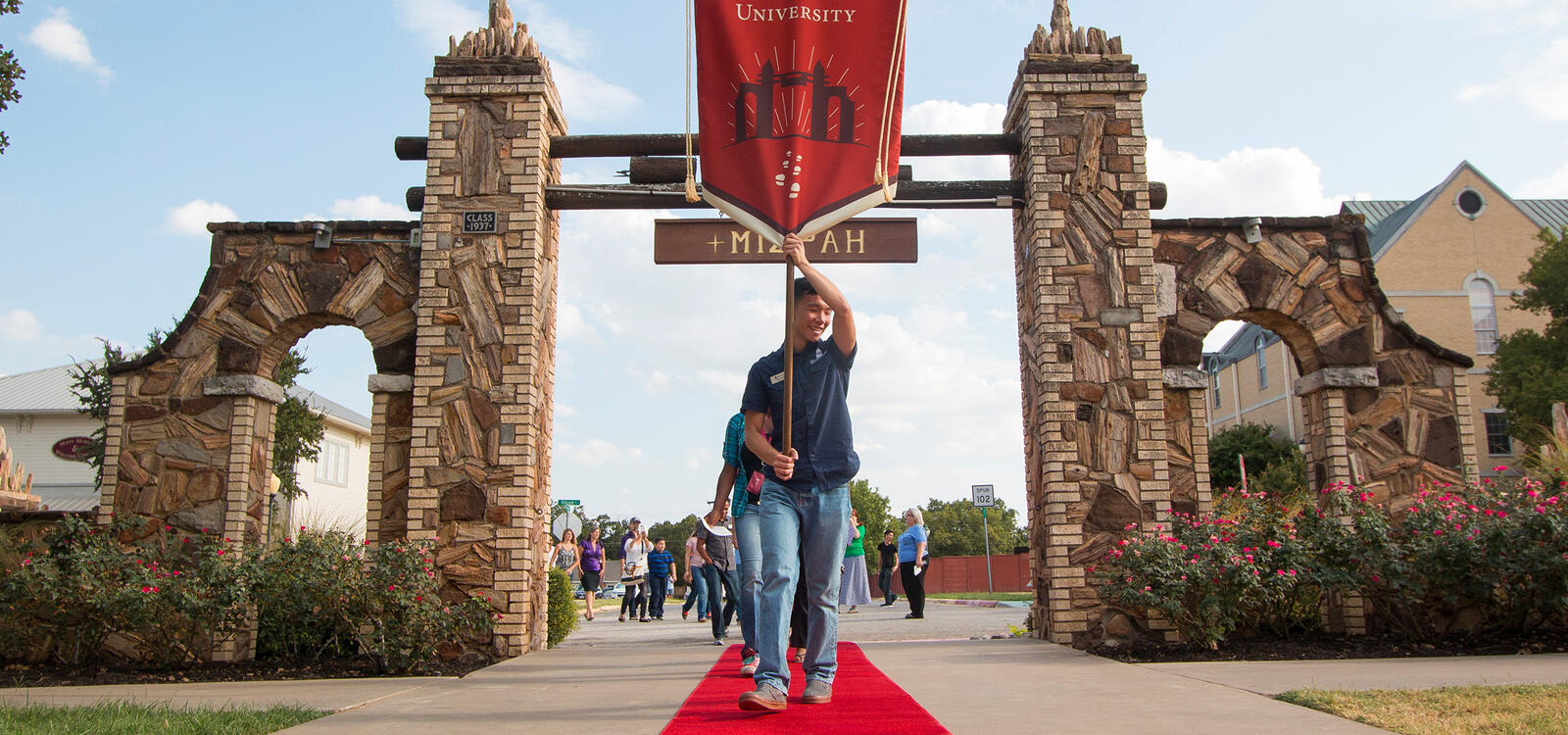 Student in front holds a SWAU banner as he leads incoming freshman down a red carpet through the Mizpah gate