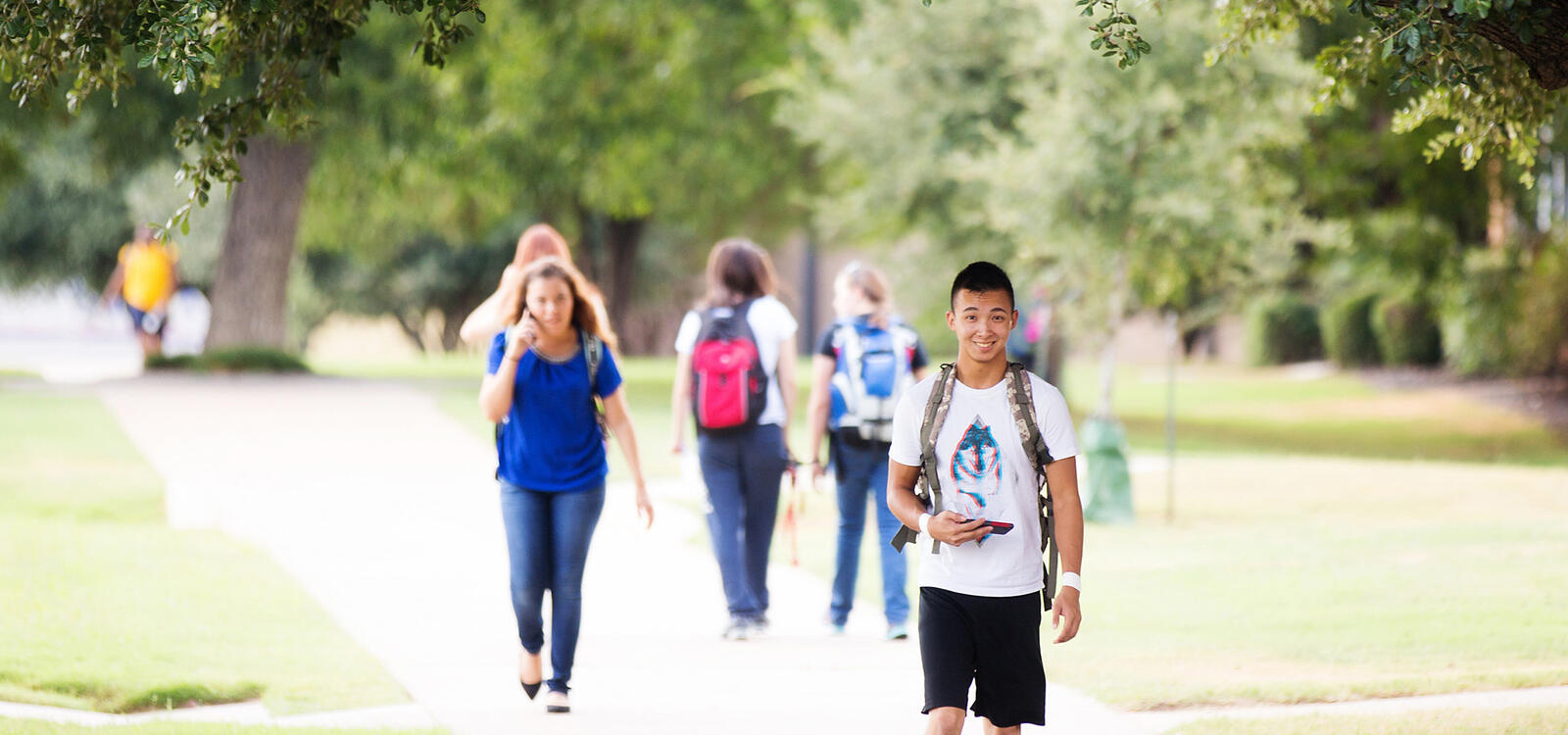 Outside on the sidewalks, students can be seen in the background walking to and from class