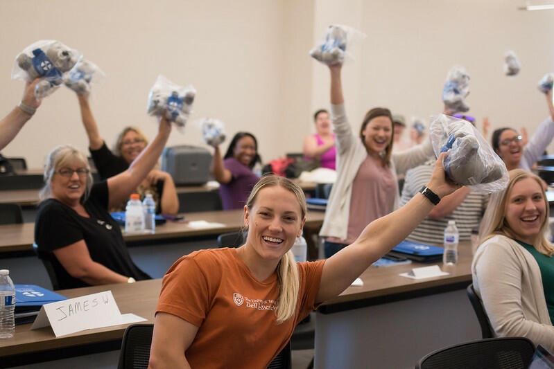 Several women sitting in a classroom holding up small, grey stuffed bears as they smile and cheer